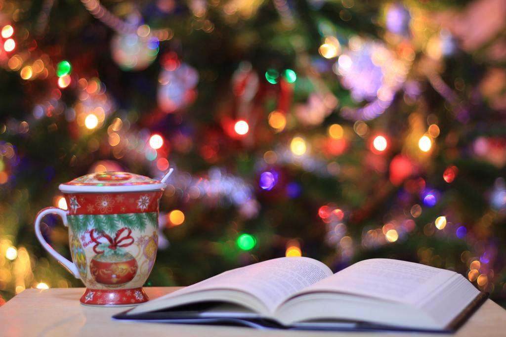 Photo of an open book and a Christmas mug next to a Christmas tree