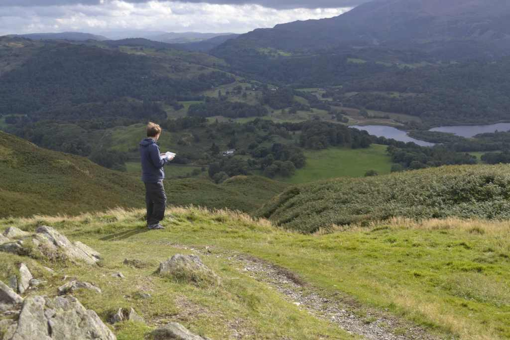 Photo shows the view from the summit of a mountain, with a man holding a map and looking ahead