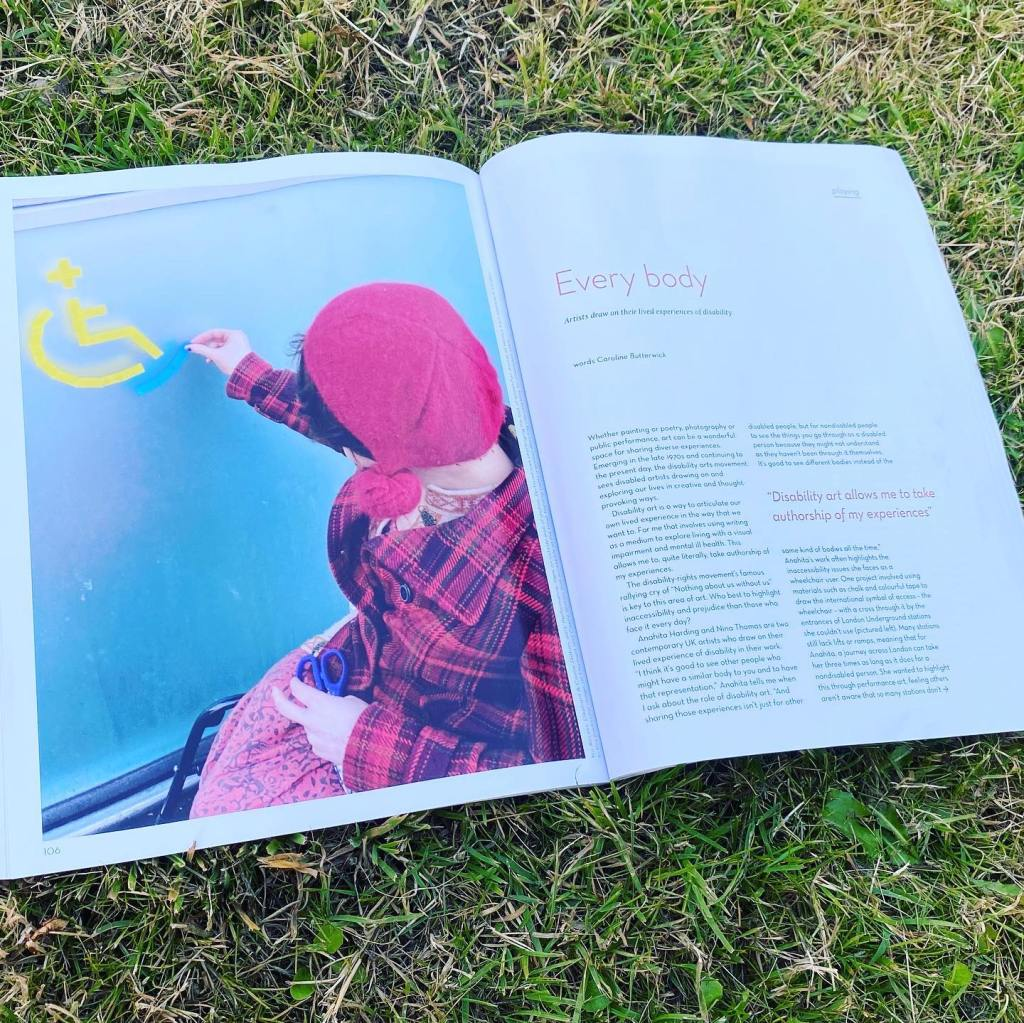 Photo shows an open magazine showing an article. The article is called Every Body. There is a photo in the magazine of a woman in a wheelchair sticking the wheelchair symbol onto a wall.