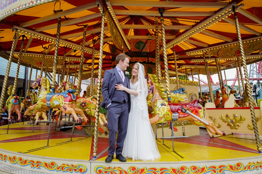 Photo shows a man in a suit and a woman in a wedding dress standing together on a carousel